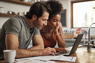 Buy stock photo Cropped shot of a couple using their laptop and going through paperwork at home