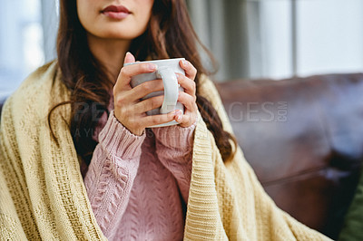 Buy stock photo Shot of a woman sitting at home with a hot beverage and a blanket