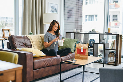 Buy stock photo Shot of a young woman eating takeout while sitting on the couch at home