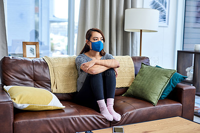 Buy stock photo Shot of a young woman wearing a fabric mask while sitting at home