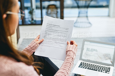 Buy stock photo Shot of a woman reading a letter of unemployment