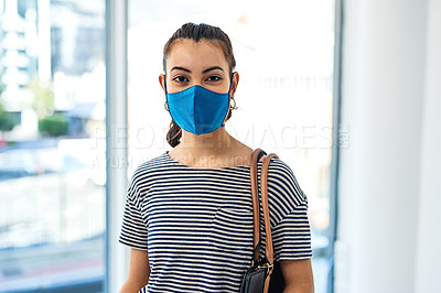 Buy stock photo Shot of a masked young woman travelling with her face mask and handbag