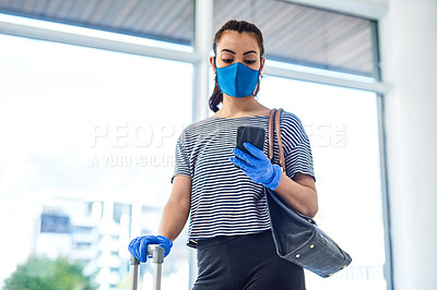 Buy stock photo Shot of a masked young woman using a smartphone in an airport