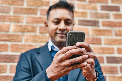 Buy stock photo Shot of a businessman using a smartphone against a city background
