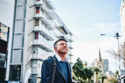 Buy stock photo Shot of a businessman standing in the city and looking up hopefully