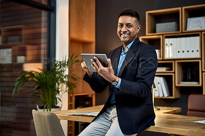 Buy stock photo Portrait of a confident businessman using a digital tablet in a modern office