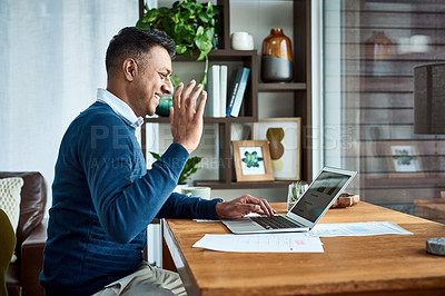 Buy stock photo Shot of a businessman using a laptop to make a video call while working from home