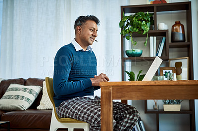 Buy stock photo Shot of a businessman using a laptop and headset while working from home