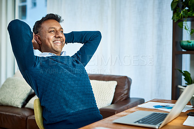 Buy stock photo Shot of a relaxed businessman using a laptop and headset while working from home