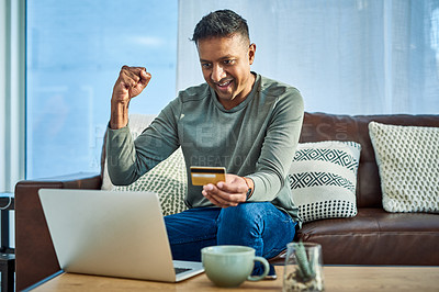 Buy stock photo Shot of a man cheering while using a laptop and credit card on the sofa at home