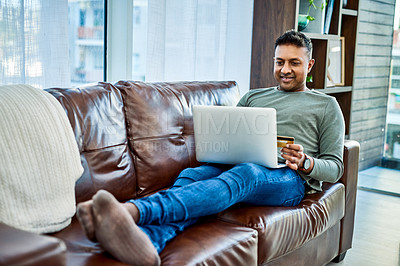 Buy stock photo Shot of a man using a laptop and credit card on the sofa at home