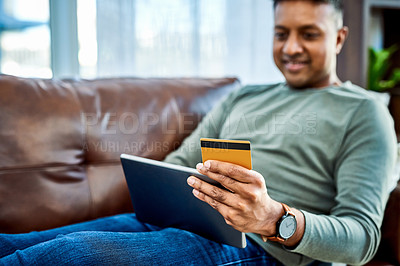 Buy stock photo Shot of a man using a digital tablet and credit card on the sofa at home