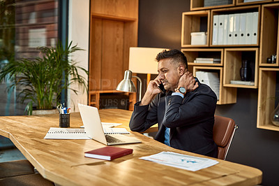 Buy stock photo Shot of a businessman looking stressed while using a laptop and smartphone in a modern office