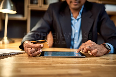 Buy stock photo Shot of an unrecognisable businessman using a digital tablet and credit card at his desk in a modern office
