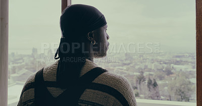 Buy stock photo Shot of a young man looking out of his apartment window