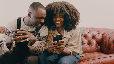 Buy stock photo Shot of a young woman using a smartphone while her husband has coffee on the sofa at home