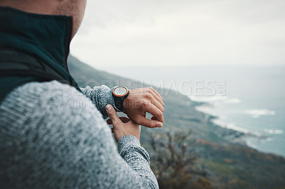 Buy stock photo Closeup shot of an unrecognisable man checking the time while out on a hike