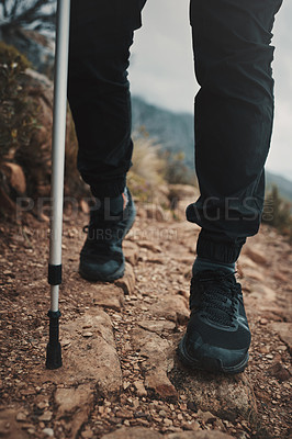 Buy stock photo Closeup shot of an unrecognisable man using a walking pole while hiking through the mountains
