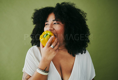Buy stock photo Studio shot of a young woman eating a yellow pepper against a green background