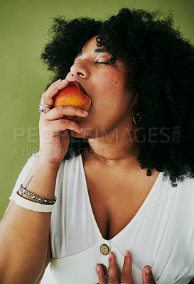 Buy stock photo Studio shot of a young woman eating a nectarine against a green background