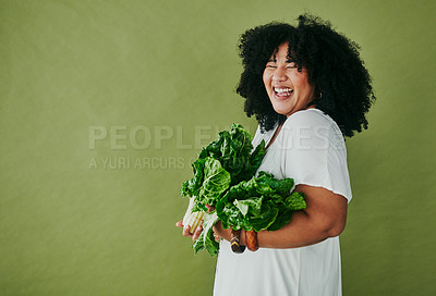 Buy stock photo Studio shot of a young woman holding a bunch of spinach against a green background