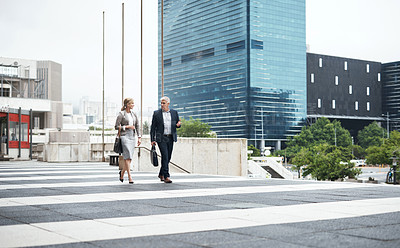 Buy stock photo Shot of two mature businesspeople having a discussion while walking in the city