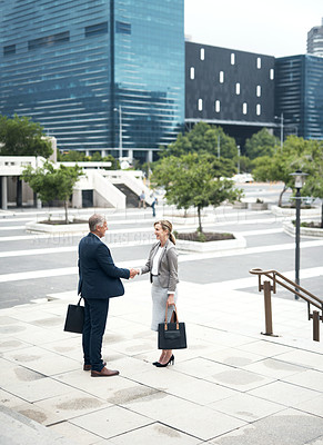 Buy stock photo Shot of two mature businesspeople shaking hands in the city