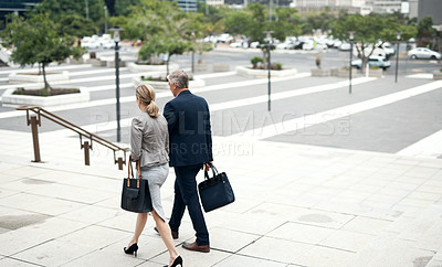 Buy stock photo Rearview shot of two businesspeople walking in the city