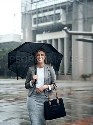 Buy stock photo Portrait of a mature businesswoman holding an umbrella while out in the city