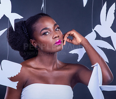 Buy stock photo Studio portrait of a beautiful young woman posing with paper birds against a black background