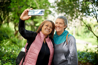 Buy stock photo Shot of two mature women taking selfies while out for a hike in nature