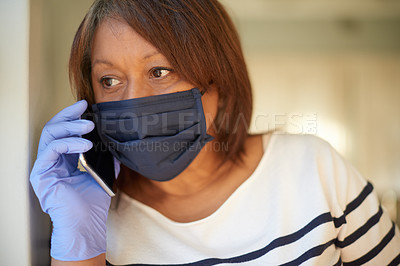 Buy stock photo Shot of a woman wearing a mask and gloves while talking on her cellphone at home