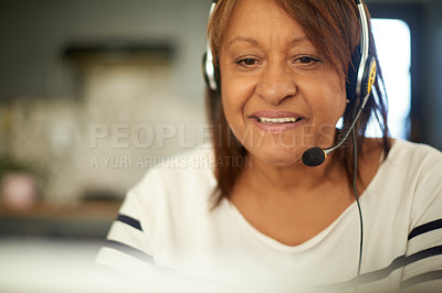 Buy stock photo Shot of a mature woman wearing a headset while working from home