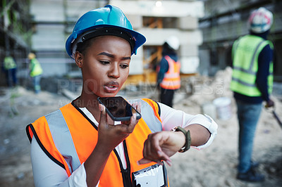 Buy stock photo Shot of a young woman using a smartphone while working at a construction site