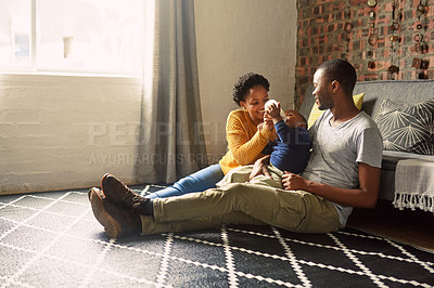 Buy stock photo Shot of a young couple spending quality time with their baby at home