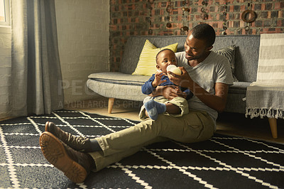 Buy stock photo Shot of a man bottle feeding his baby at home