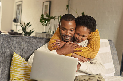 Buy stock photo Shot of a man using his laptop while his girlfriend embraces him from behind