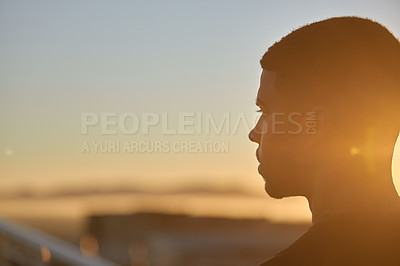 Buy stock photo Rearview shot of a sporty young man looking thoughtful while exercising outdoors