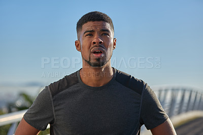 Buy stock photo Shot of a sporty young man catching his breath while exercising outdoors