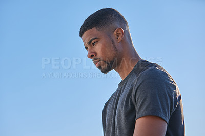 Buy stock photo Shot of a sporty young man looking thoughtful while exercising outdoors