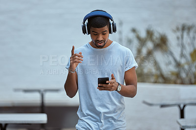 Buy stock photo Shot of a young man using a smartphone and headphones against an urban background