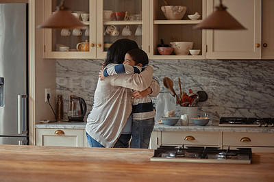 Buy stock photo Shot of a woman and her young son embracing each other in the kitchen at home