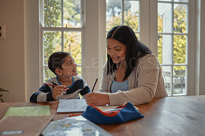 Buy stock photo Shot of a young mother helping her son with his homework at home