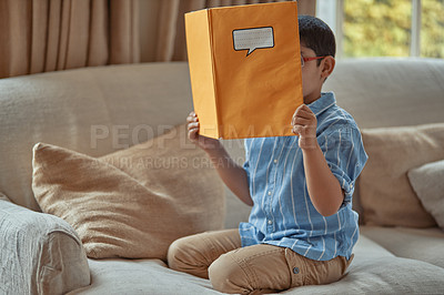 Buy stock photo Shot of a young boy holding up a book over his face