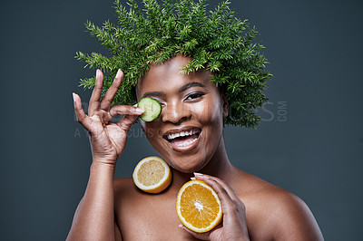 Buy stock photo Shot of a woman wearing a leaf wreath while holding cucumber, lemon and an orange against her skin