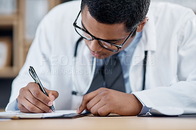 Buy stock photo Shot of a young doctor writing notes on a clipboard in an office