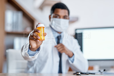 Buy stock photo Closeup shot of an unrecognisable doctor holding a bottle of pills in his office