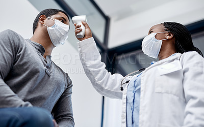 Buy stock photo Shot of a doctor taking a patient's temperature with an infrared thermometer
