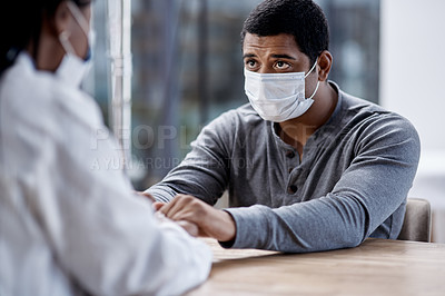 Buy stock photo Shot of a young man holding hands with a doctor during a consultation