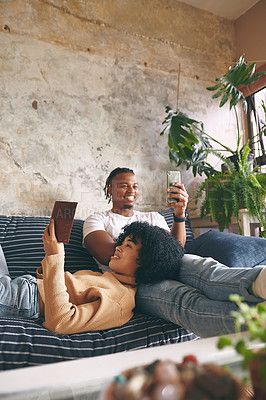 Buy stock photo Shot of a young woman reading a book while her boyfriend uses a cellphone at home